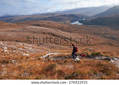 A hiker and their dog descending the summit of Beinn Eighe with Loch Clair in the distance. The Scottish Highlands. - stock photo