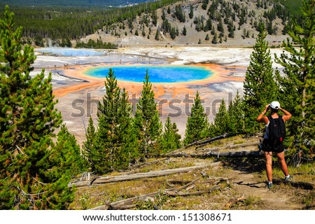 A hiker looking down on Yellowstone National Park's Grand Prismatic Spring in Yellowstone National Park, the largest hot spring in the United States, and the third largest in the world.  - stock photo
