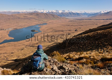 A Hiker Looks Over Lake Clearwater Towards The Southern Alps.  Hakatere Conservation Park, Lake Clearwater, New Zealand - stock photo