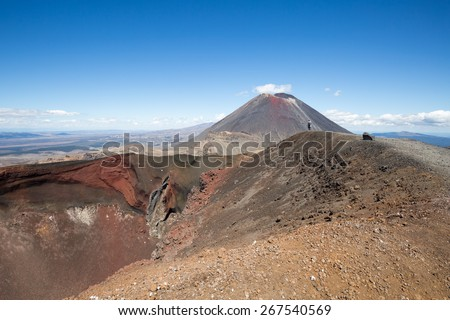 A hiker on red crater in Tongariro, New Zealand, looking at Mount Ngauruhoe - stock photo