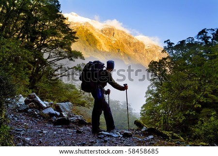 A hiker pauses for a rest at a clearing while ascending into the mountains - stock photo