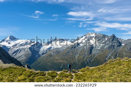 A hiker posing infront of distant range, New Zealand. - stock photo