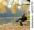 A hiker sitting on the bench near river - stock photo