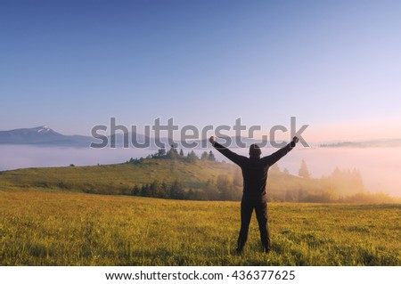 A hiker stands with raised hands in a mountain valley. Misty sunrise. Spring time.