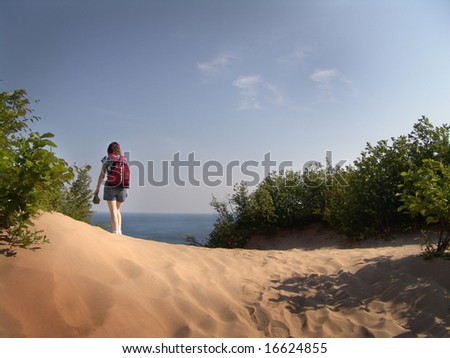 A Hiker strolling over a dune. - stock photo