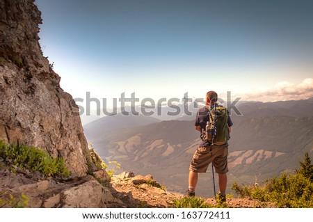 A hiker takes a break to enjoy the view - stock photo