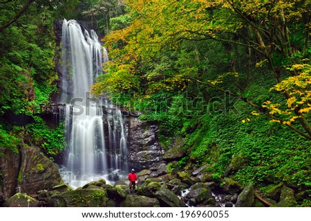 A hiker taking in the beauty of a waterfall in a lush, green forest. - stock photo