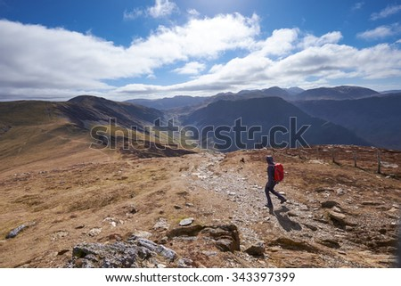 A hiker walking down Little Edge towards Hindscarth with Honister Pass in the distance, English Lake District, UK.                                - stock photo