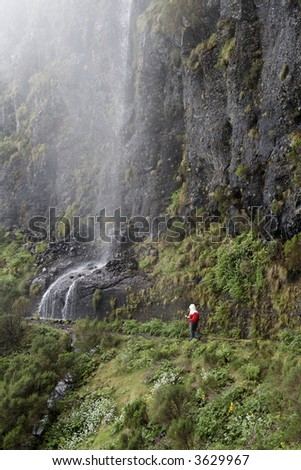 A hiker walks in mountain landscape with waterfall and fog on Madeira Island - stock photo