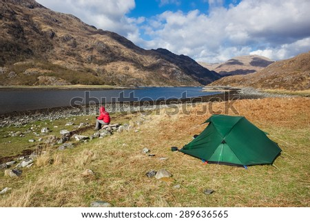 A hiker wilding camping at Barrisdale Bay beside Loch Hourn in the Scottish Highlands. - stock photo