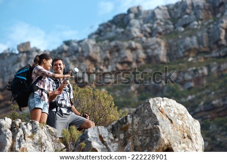 A hiking couple looking at the beautiful view on a mountain with copyspace - stock photo