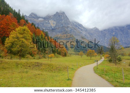 A hiking path through the meadow with maple trees on the mountainside ~ Beautiful autumn scenery of Karwendel Mountains in Eng, Hinterriss, Austria ~ European alps ~ - stock photo