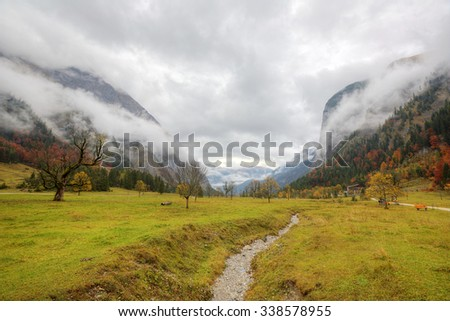 A hiking path through the meadow with maple trees on the mountainside under cloudy moody sky ~ Beautiful autumn scenery of Karwendel Mountains in Eng, Hinterriss, Austria ~ European alps - stock photo