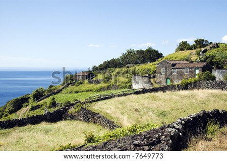 A hilly landscape with a small house next to an ocean. Taken in Azores, Portugal.