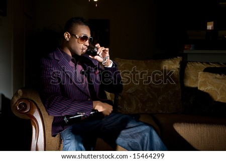 a hip young african american knocks back some wine on the couch while holding onto his bottle.