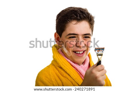 A Hispanic boy wears a yellow bathrobe with a pink towel around his neck: he has some patches on his face and smiling stares at the razor he used for shaving - stock photo
