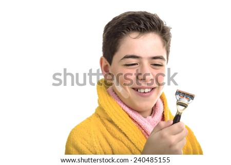 A Hispanic boy wears a yellow bathrobe with a pink towel around his neck: he has some patches on his face and smiling looks at the razor he used for shaving - stock photo