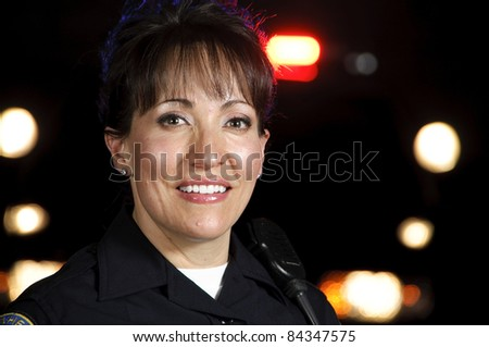 A Hispanic female officer standing in the night with her patrol car. - stock photo