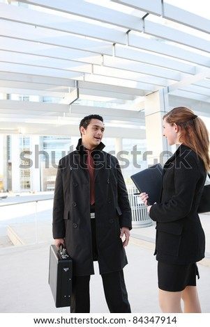 A Hispanic Man and Caucasian Business Woman at their company building - stock photo