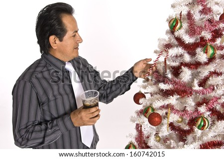 A Hispanic man in a dress shirt and tie, holding a drink, while looking at a decorated Christmas tree. - stock photo