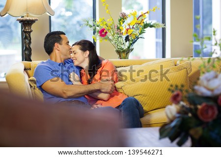 A hispanic man kisses  caucasian woman on her forehead wearing jeans and sitting on a yellow couch in their living room. - stock photo