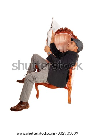 A Hispanic man sitting in a armchair reading his newspaper wearing acap, isolated for white background. - stock photo
