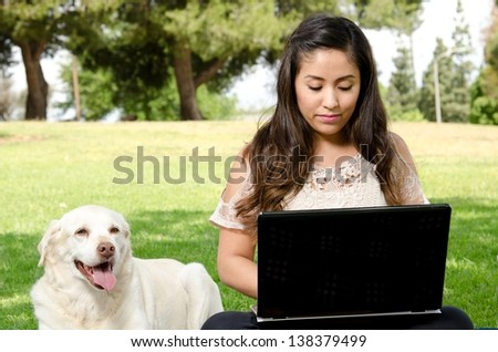 a Hispanic woman sitting in the park with her dog and her computer. - stock photo
