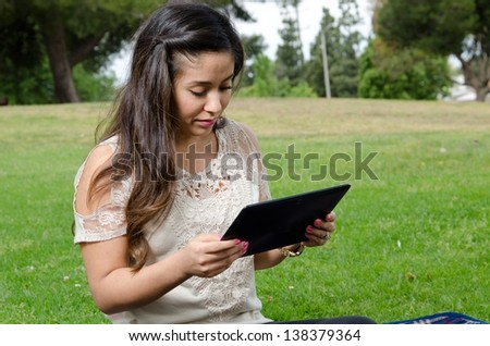 A Hispanic woman sitting in the park with her tablet.