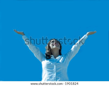 A hispanic woman with arms extended to the sky. - stock photo