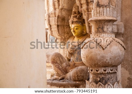 A historic ancient statue outside in the courtyard of the famous Buddhist temple of Ananda in Bagan, Burma