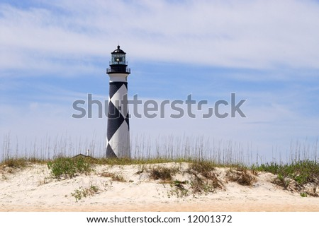 A historic lighthouse guiding ships away from rocky shoals. - stock photo