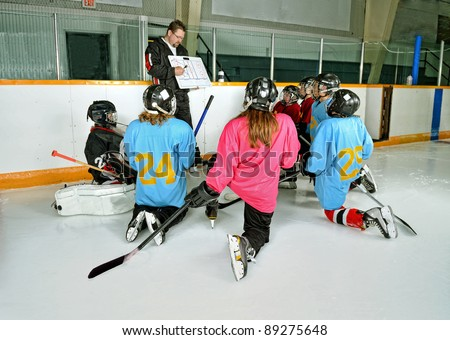 A Hockey Coach at practice teaches game plan to team players - stock photo