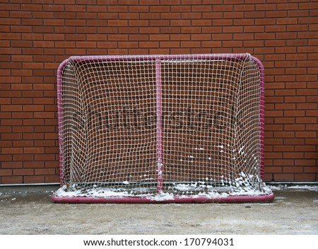 A hockey net against a brick wall - stock photo