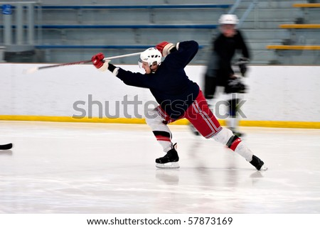 A hockey player shooting the puck as he speeds down the ice.  Slight motion blur. - stock photo