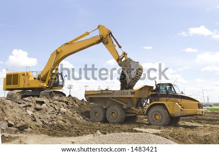 A hoe filling up a dump truck - stock photo