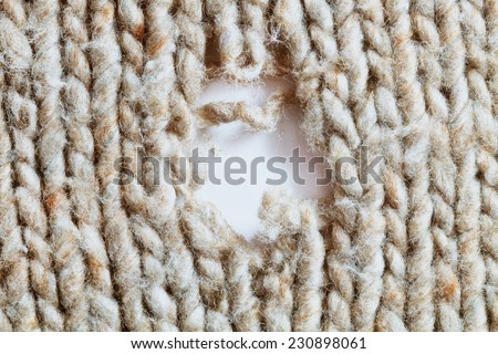 A hole in a damaged wool garment - stock photo