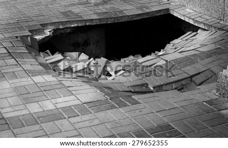 A hole in pedestrian pavement road - stock photo