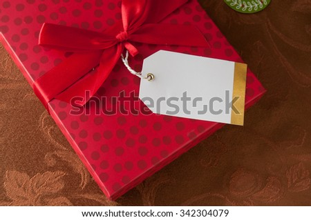 A holiday gift with bow and a blank tag