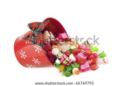 A holiday red bucket full of hard Christmas candy spilling out, isolated on white background - stock photo