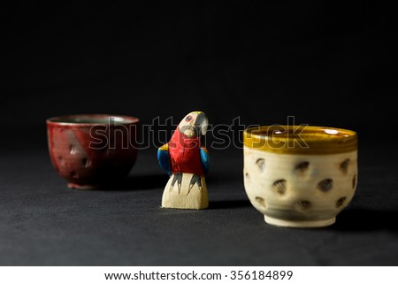 a Holzpapagay between two clay bowls - stock photo