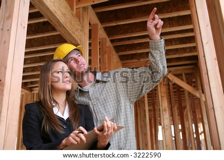 A home construction worker pointing out something for the client - stock photo