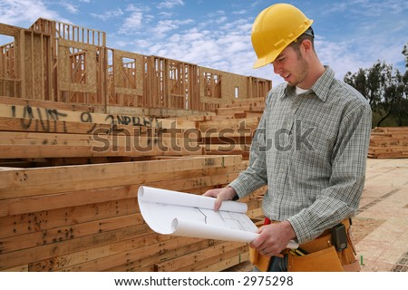 A home contractor holding blueprints outside a home in progress - stock photo