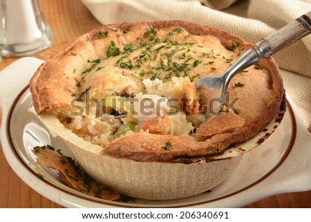 A home cooked turkey pot pie with carrots, potatoes and peas - stock photo