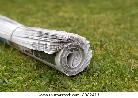 A home delivered newspaper on the lawn. - stock photo