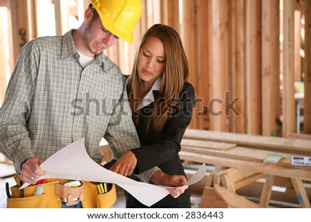 A home designer working with a home builder and inspecting the blueprints - stock photo