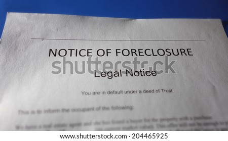 A home foreclosure document on blue background                                - stock photo