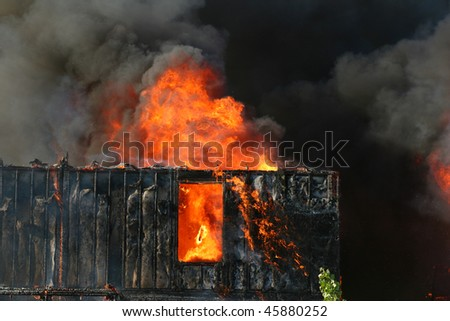 A home, fully engulfed by fire. - stock photo