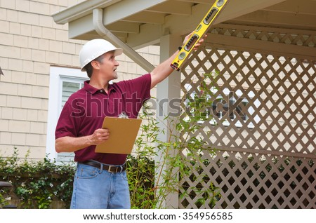 A home inspector or house building repair contractor in a hard hat holding a level and a clipboard outside a home doing an inspection or construction quote - stock photo
