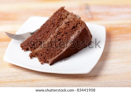 A home made slice of chocolate cake on a white plate with a fork.  Shallow depth of field with focus on the front of the cake. - stock photo
