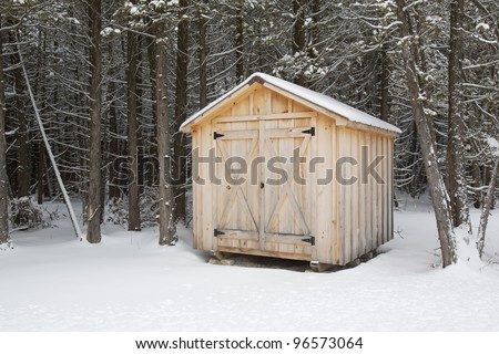 A home made wood shed with forest behind, in winter. - stock photo